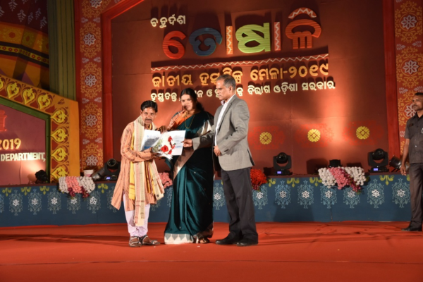 Hon, ble Minister, Handlooms, Textiles & Handicrafts, Odisha felicitating Sri Arjun Meher, Barapali, Dist- Baragarh on 15/12/2019 in Presence of the Commissioner-cum- Secretary to Govt HT&H Dept.